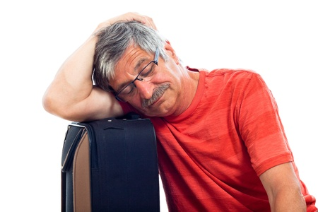 Tired senior man sleeping on luggage, isolated on white background. photo