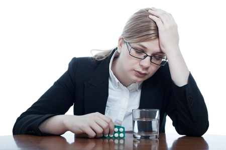 Unhappy business woman with headache holding painkillers, isolated on white background. photo