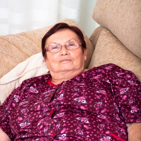 Close up of elderly woman relaxing on sofa. photo