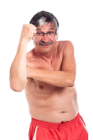 disrespectful: Funny shirtless senior man gesturing with fist, isolated on white background.