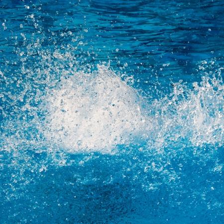 Cancella spruzzata pura acqua sulla superficie blu brillante. Archivio Fotografico - 15311566