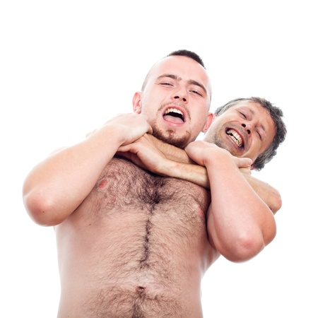 Two funny shirtless men wrestling, isolated on white background. photo