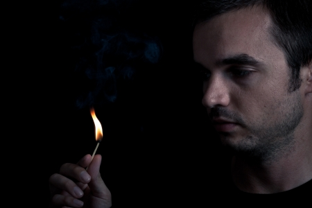 Dramatic portrait of man lighting safety match, over black background. Stock Photo