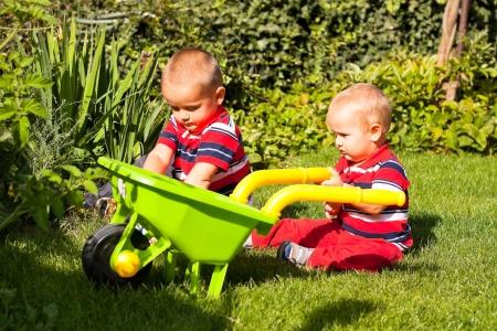 Dos hermanos que juegan en el jardín durante el día soleado. Foto de archivo - 15572357