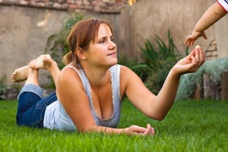 Portrait of a young woman lying on grass and giving sometime sweet to child. photo