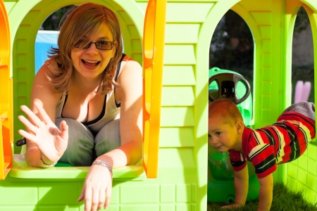 Happy woman and little boy having fun in colorful playhouse.