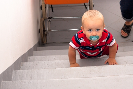 Photo of cute baby boy on stairs. photo