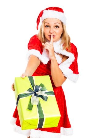 Young attractive blond woman giving gift box, wearing Christmas Santa costume and gesturing silence, isolated on white background.