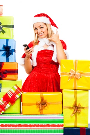 Young blond happy woman wearing Christmas Santa costume with mobile phone, surrounded by gift boxes, isolated on white background. Stock Photo - 16008553