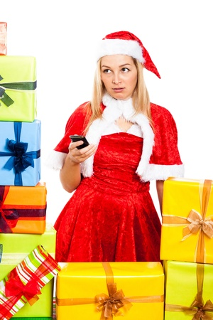 Young blond worried woman wearing Christmas Santa costume holding mobile phone, surrounded by gift boxes, isolated on white background. photo