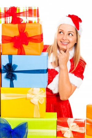 Young blond happy cute woman in Santa costume surrounded by Christmas gift boxes, isolated on white background. Stock Photo - 16008548
