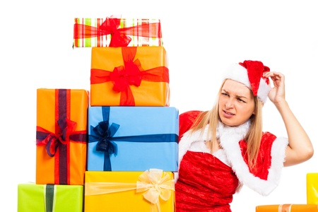 Young blond worried woman in Santa costume surrounded by Christmas gift boxes, isolated on white background. Stock Photo - 16008542