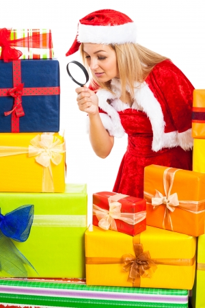 Young blond beautiful woman in Santa costume exploring Christmas gift boxes with magnifying glass, isolated on white background. Stock Photo - 16008532