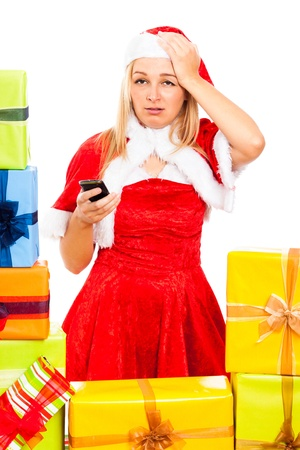 Young blond unhappy woman wearing Santa costume holding mobile phone, surrounded by Christmas gift boxes, isolated on white background. photo