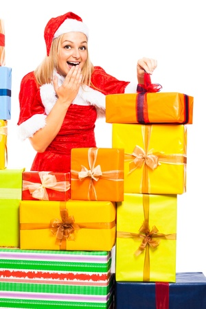 Young beautiful blond cute happy woman in Santa costume opening Christmas gift boxes, isolated on white background. Stock Photo - 16120502