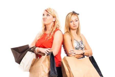 Two young blond unhappy women holding shopping bags, isolated on white background
