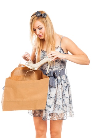 Young beautiful blond woman holding shoe and shopping bag, isolated on white background  photo
