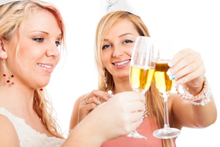 Close up of two young happy women celebrating with glasses of Champagne, isolated on white background. photo