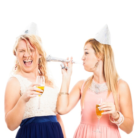 Two young women celebrating with party horn, isolated on white background. photo