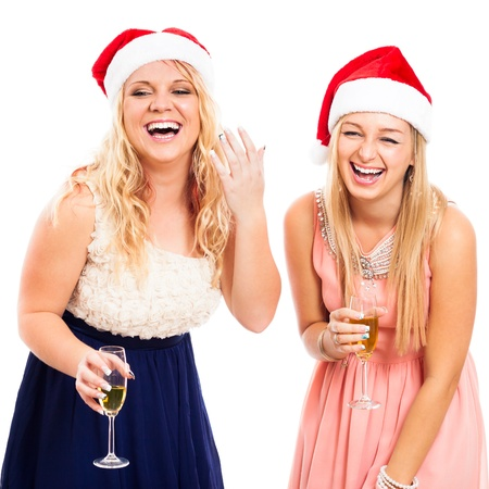 Two young blond laughing women celebrating in Christmas hat, isolated on white background. photo