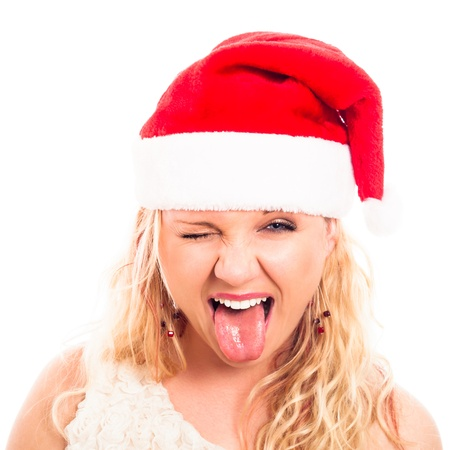 Close up of young woman in Santa hat making funny faces, isolated on white background. photo