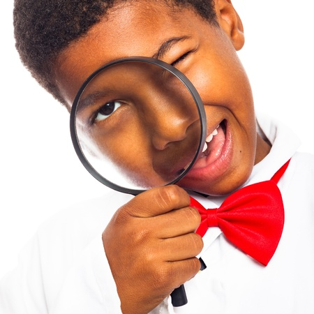 Close up of clever scientist school boy with magnifying glass, isolated on white background.