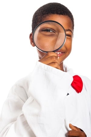 Happy clever scientist school boy with magnifying glass, isolated on white background.