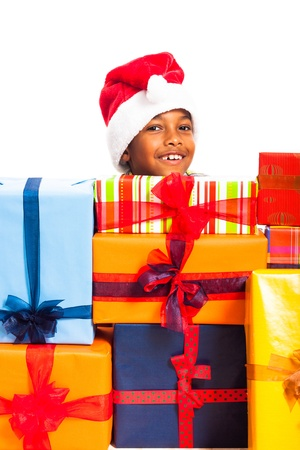 Happy cute child boy in Santa hat surrounded by colorful Christmas gift boxes, isolated on white background. photo