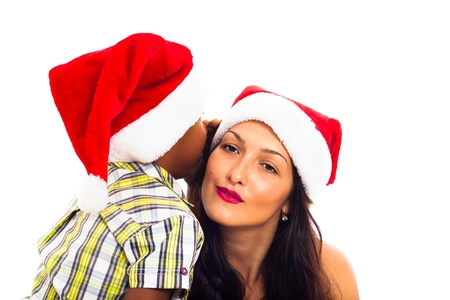 Beautiful young woman and child boy in Christmas hat whispering, isolated on white background. photo