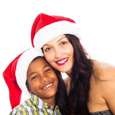 Close up of young beautiful happy woman and child boy wearing Christmas hat, isolated on white background. photo