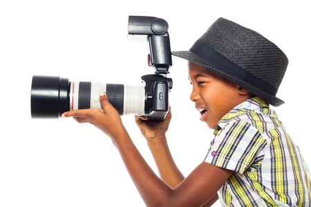 Child boy taking photo with professional camera, isolated on white background. Stockfoto