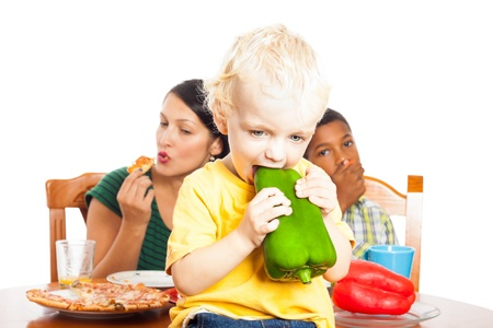 mealtime: Cute child eating healthy green pepper and woman with boy eating pizza, isolated on white background. Stock Photo