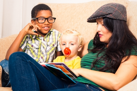 Young happy woman with children reading book and relaxing on sofa. photo