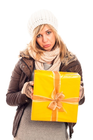 Unhappy disappointed sad woman holding yellow gift box, isolated on white background. photo