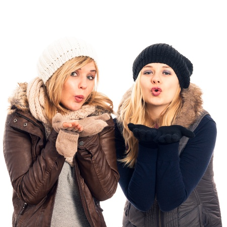 women kissing women: Two young happy women in winter clothes sending kiss, isolated on white background.