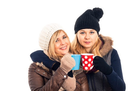Two young happy women in winter clothes holding mug with hot drink, isolated on white background.