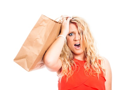 Young attractive blond shocked woman holding shopping bag, isolated on white background. Stock Photo - 16522461