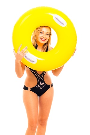 monokini: Portrait of young beautiful happy woman in swimsuit holding yellow rubber ring, isolated on white background.