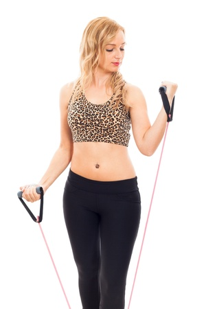 rubber bands: Young fitness woman exercising and stretching rubber band, isolated on white background. Stock Photo