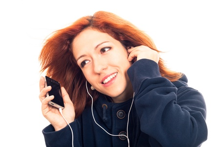 Young woman in blue hoodie holding smartphone and listening music, isolated on white background. photo