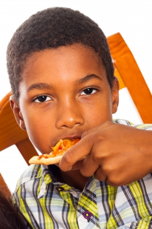 Close up of little boy eating pizza. photo