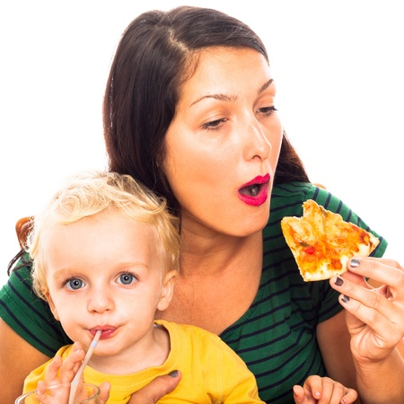 Young hungry woman eating pizza and child boy drinking, isolated on white background. photo