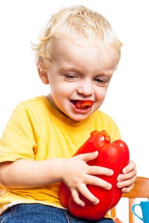 Happy child boy biting red sweet pepper, isolated on white background. Stock Photo - 16959773