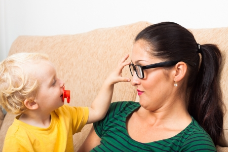 Young woman wearing eyeglasses with child boy playing on sofa. Stock Photo - 16960480