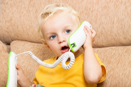 Close up of cute child boy using telephone. photo