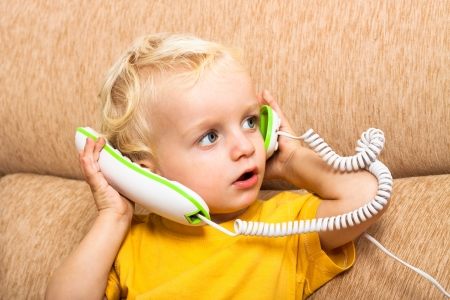 Close up of cute child boy playing with telephone. photo