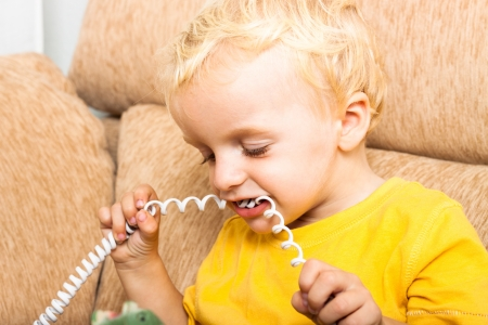 Close up of child boy biting phone wire. Stock Photo - 16960475