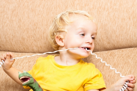 Close up of funny child boy biting phone wire. photo