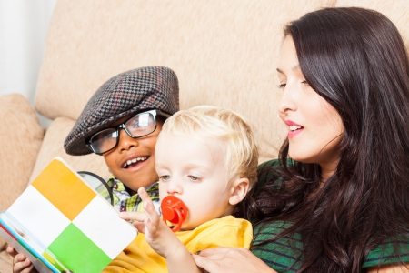 Young happy woman with children reading book. Stock Photo - 16960485