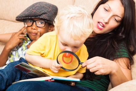 Young woman and children reading book with magnifying glass. Stock Photo - 16960484